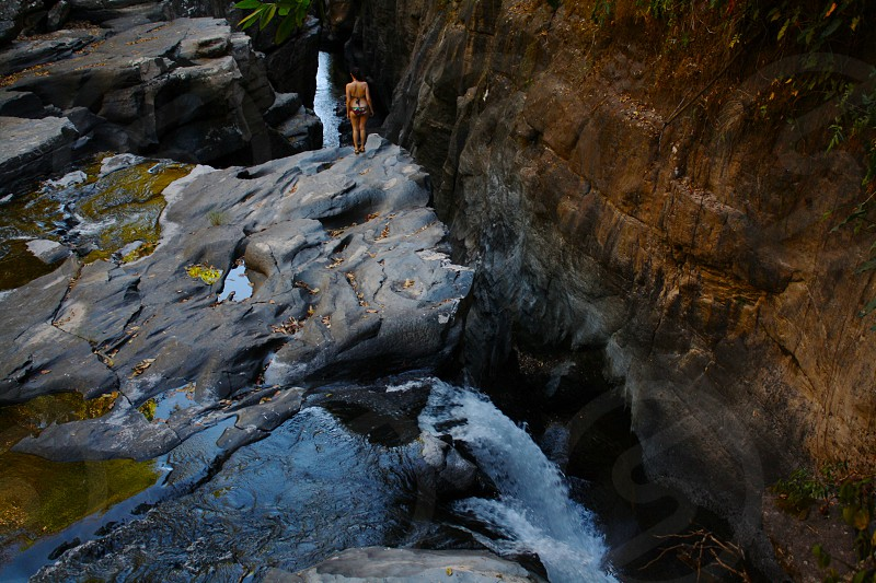 woman in multicolor bikini on rock cliff near flowing water photo