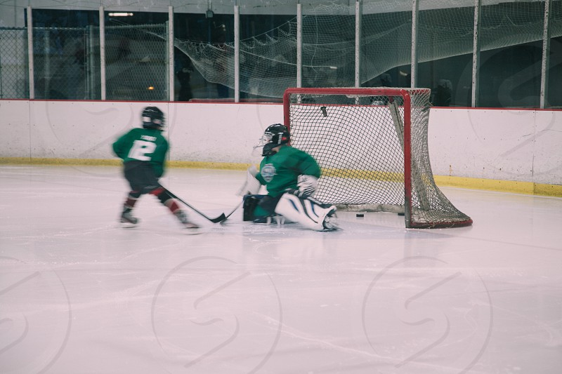 2 people playing ice hockey game photo