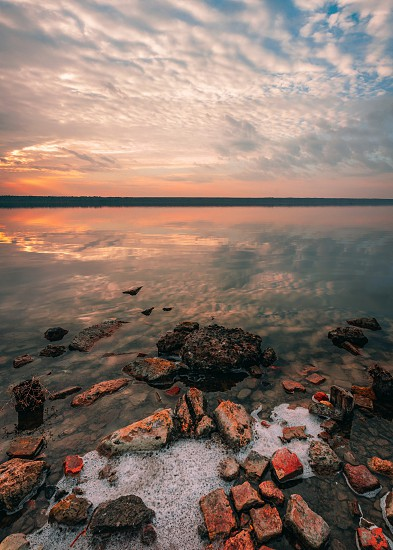 Stones on the lake in the red light of summer sunset photo