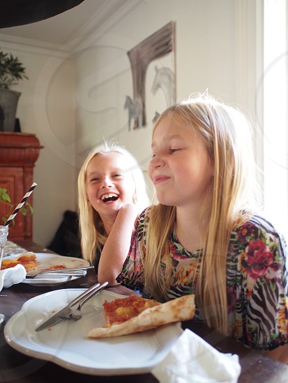 Telling a story laughing happy friends young girls two persons pizza table plates glass child kids  photo