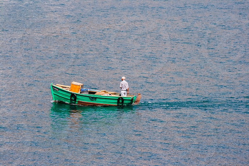 aerial photography of man standing on green bass boat in the middle of body of water during daytime photo