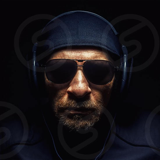 Portrait of a man wearing a headphones strong face and beard details.  photo