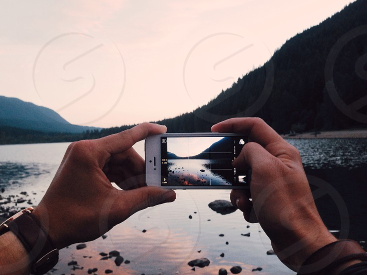 human taking a photo of a lake using a smartphone photo