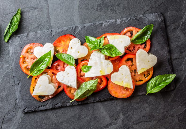 Mediterranean Italian Caprese salad with tomatoes and cheese mozzarella cut as hearts and basil on stone slate plate on slate background. Valentine day menu consept. Healthy food. Top view photo