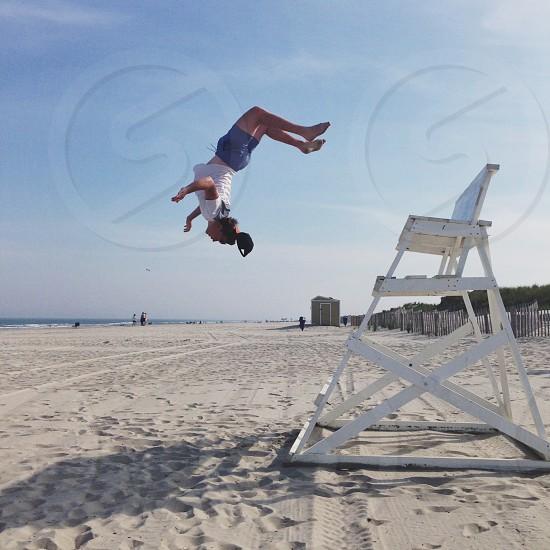woman in white t shirt doing back flip on beach photo