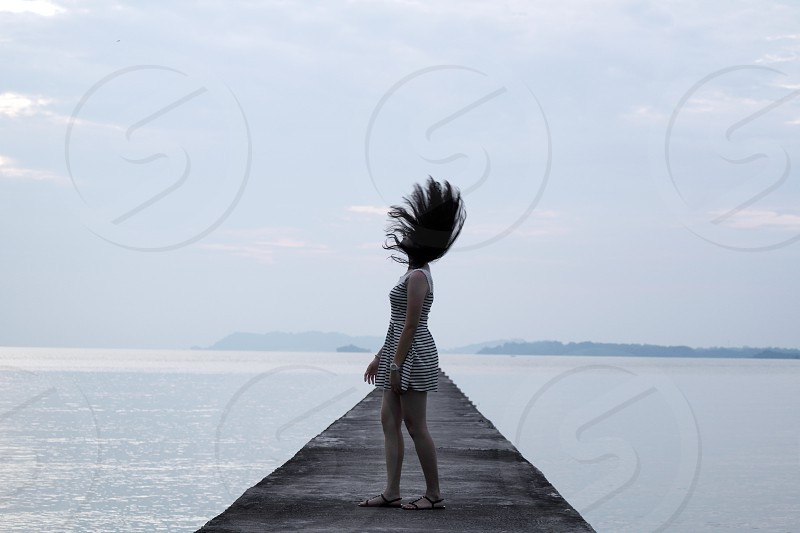 woman in mini dress standing on concrete walkway on seawater under white cloudy sky photo