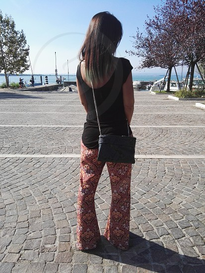 woman in black tank top and red and white floral pants wearing black sling bag standing on gray pavement between trees under blue clear sunny sky photo