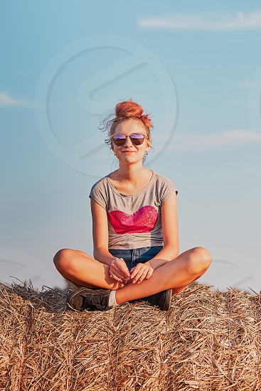 Happy smiling teenage girl sitting on a hay bale at sunset enjoying summer vacations in the countryside. Candid people real moments authentic situations photo