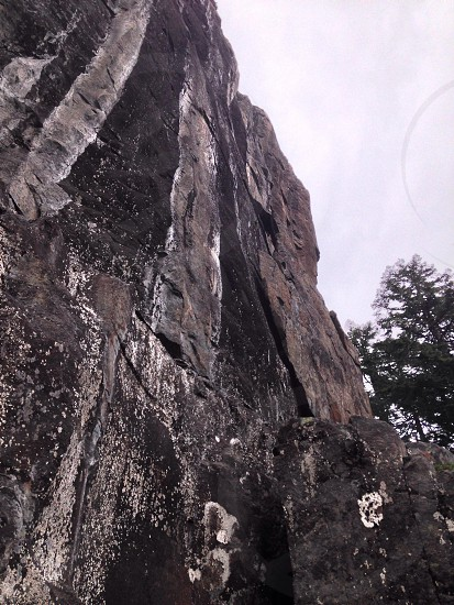 low-angle view of a tall grey steep rock cliff under grey cloudy sky during daytime photo