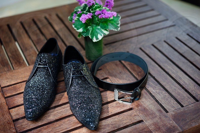 Luxury glitter shiny men's shoes with leather belt on the wooden table vase of flower in background photo