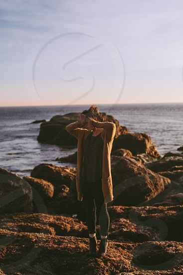 woman in black halter top black pants and brown cardigan standing on brown rock by the ocean under blue clear sky photo