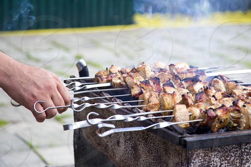 Grilled kebab cooking on metal skewer. Roasted meat cooked at barbecue. Traditional eastern dish shish kebab. Grill on charcoal picnic street food photo
