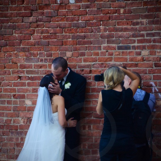 man kissing a woman in a wedding dress photo