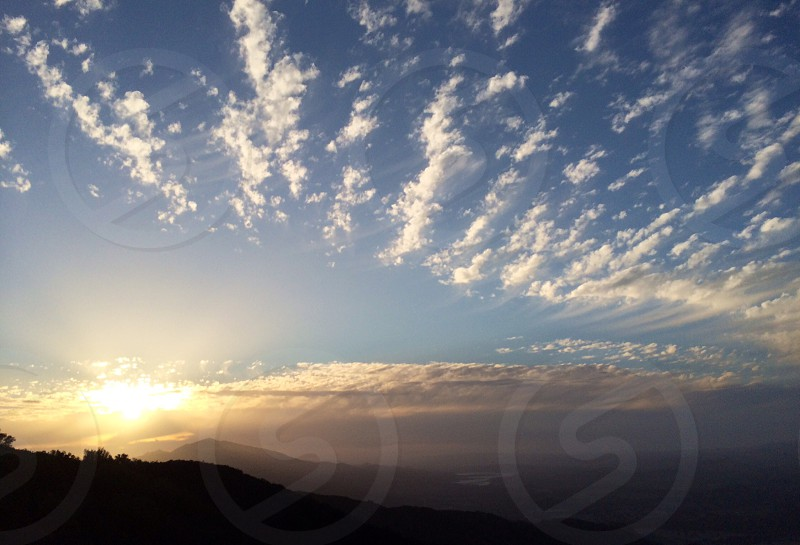 mountain silhouette with sun rays and blue sky photo
