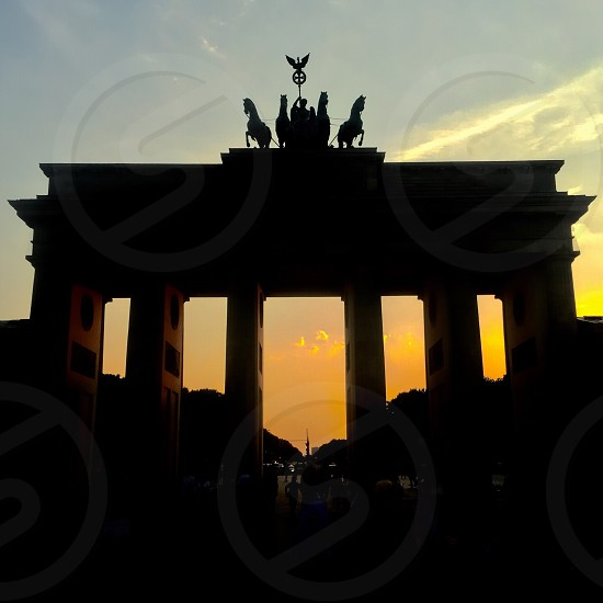 silhouette of brandenburg gate under yellow sunset photo