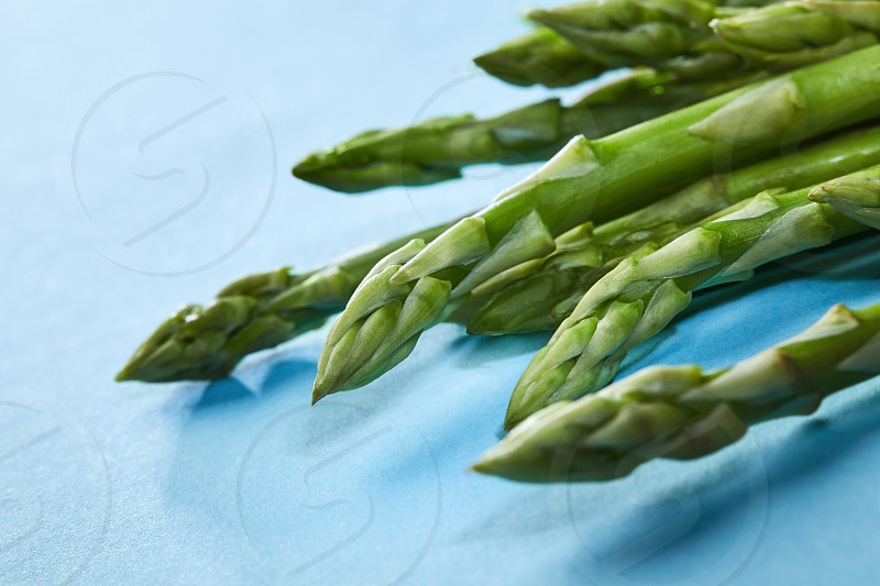 Spring season - fresh green asparagus on the blue background. Concept healthy clean eating. Flat lay photo