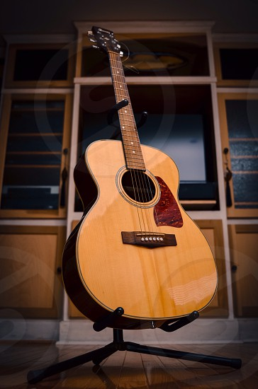 brown acoustic guitar on black stand photo