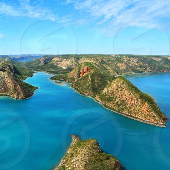 several green-and-brown islands with blue waters in between under blue skies photo