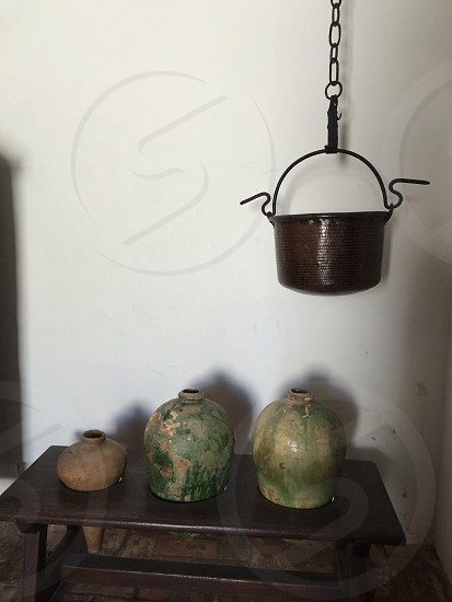 cooking pot hanging near wall with jars underneath photo
