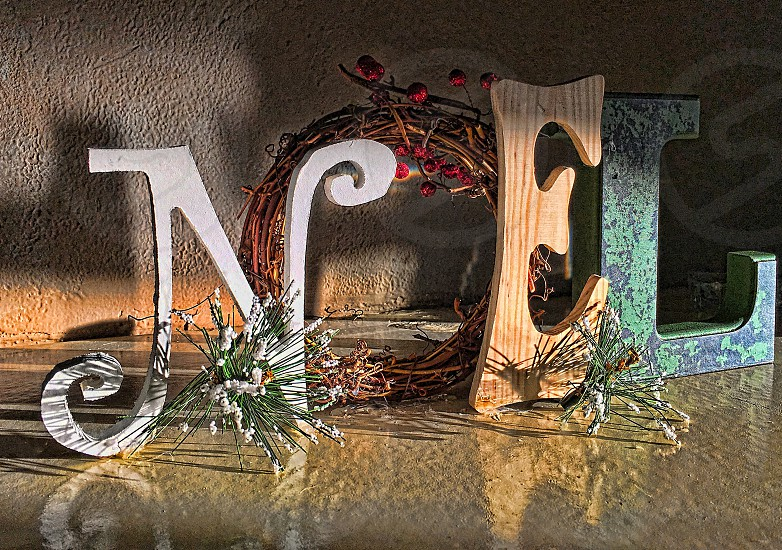 """Christmas decorated letters spelling """"NOEL"""" are reflected on a shiny surface photo"""
