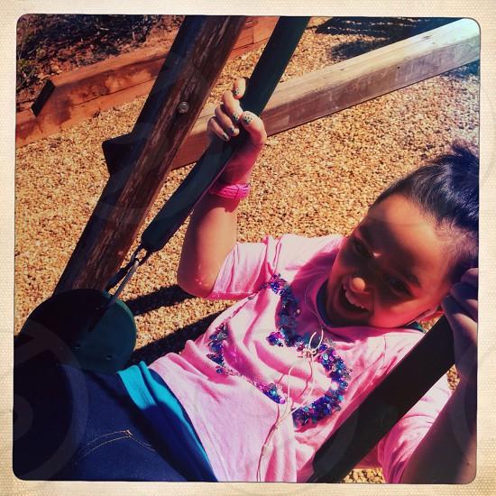 Little girl on swing in backyard photo