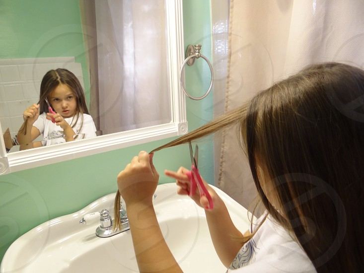Little girl about to cut her hair on her own bad decision  photo