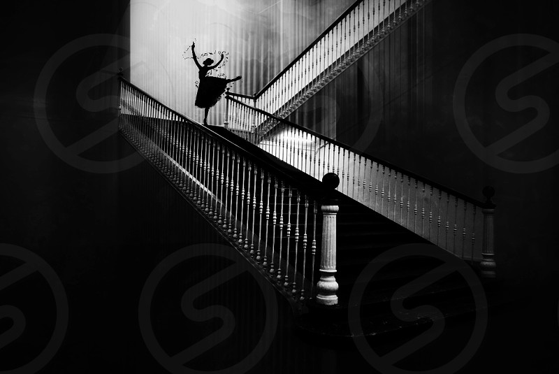 grayscale photo of woman in ballet form near wooden balustrade in stairs photo