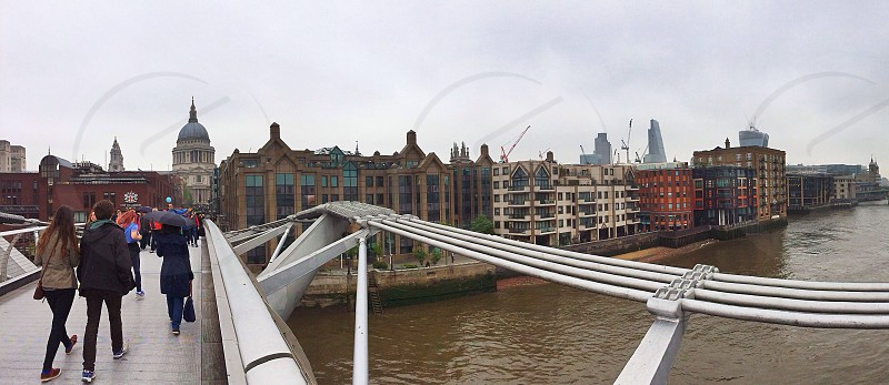 Wide panoramic shot of people crossing the Millennium Bridge London with views along the River Thames and Saint Paul's Cathedral.  photo