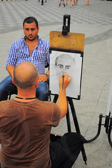 man wearing a blue and white checked shirt having his portrait drawn photo