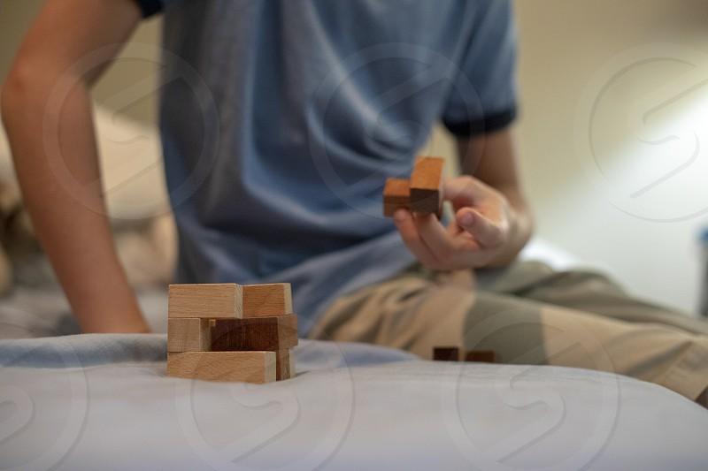 Child assembles wooden puzzle block photo