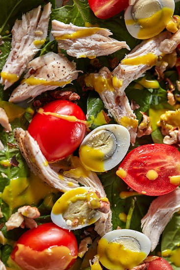 Background from natural organic color ingredients of freshly cooked salad - fresh green vegetables tomatoes cherry chicken meat quail eggs and mustard sause. Close-up view from above. photo