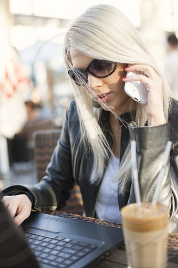 Young woman girl working on lap top and speaking on the phone outdoor with coffee photo