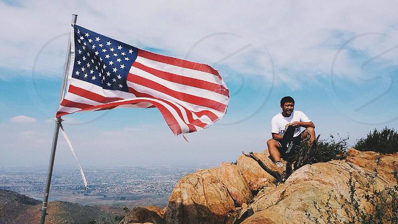 man sitting on brown stone near U.S.A flag photo