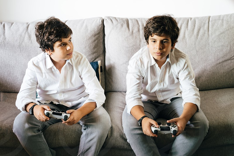 Identical twin boys playing with videogames joystick sitting on couch photo