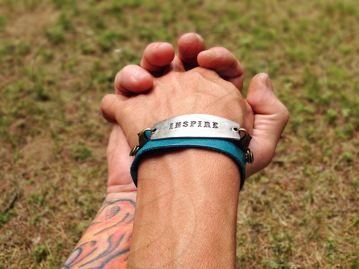 two people holding hands with silver inspire bracelet photo