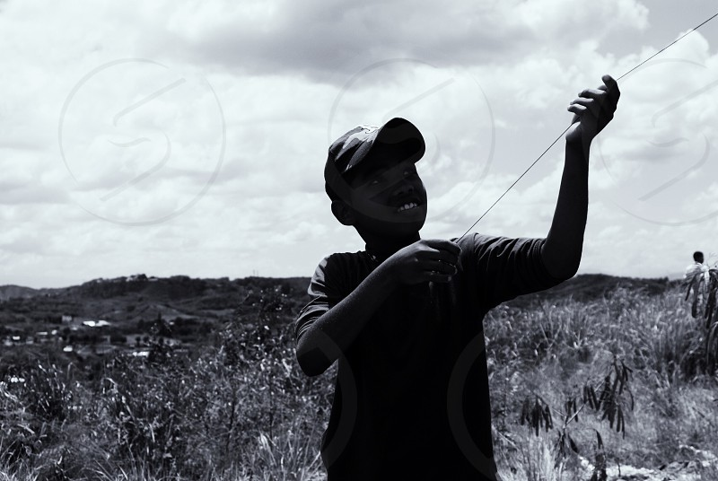 silhouette of boy holding treadle near green grass during daytime photo