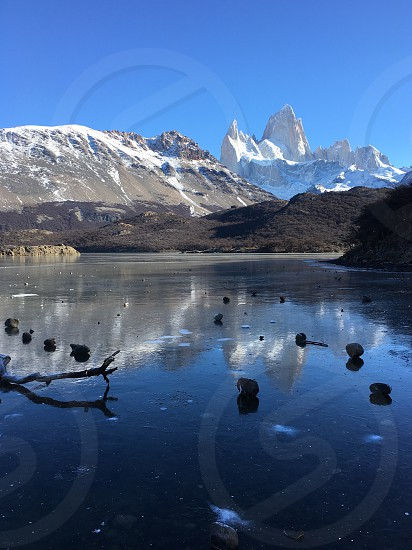 Fitz Roy Patagonia El Chalten Argentina ice snow winter cold frozen lake frozen lake snow capped mountains hill tree trunk stones reflection water reflections sky clear no clouds photo