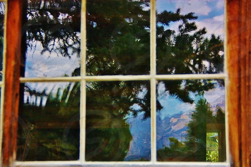 Reflection in a window of a cabin where you can also see out the back of house. photo