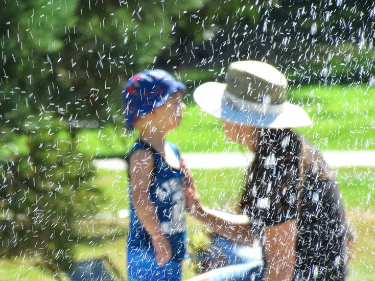 A mother reassuring her young son at the waterpark. Wearing hats on a summer day the mother places her hand on the child's heart. Landscape photo. Water droplets falling throughout the scene. Field and trees in the background.  photo