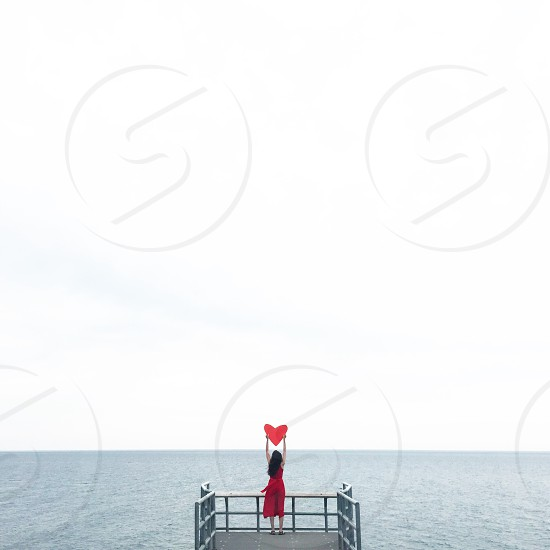 woman in red dress holding heart paper cutout standing on gray steel balcony facing the ocean photo
