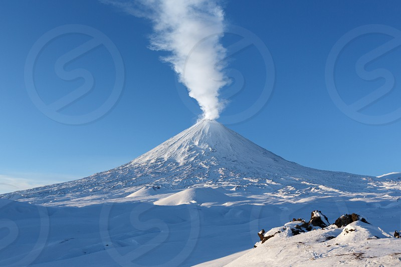 Winter volcanic landscape of Kamchatka Peninsula: view of eruption active Klyuchevskoy Volcano (Klyuchevskaya Sopka) - emission from crater of volcano plume of steam gas and ashes. Russian Far East. photo