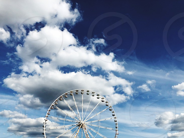 A Ferris wheel in front of a blue sky photo