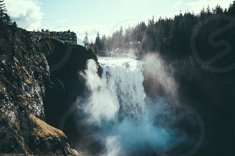 concrete buildings and trees near waterfalls photo