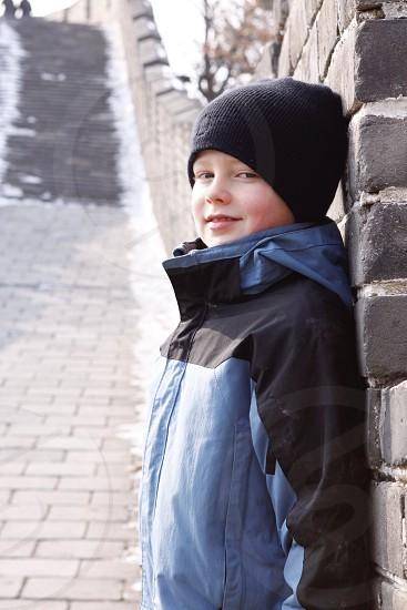 boy in blue and black jacket wearing black beanie photo