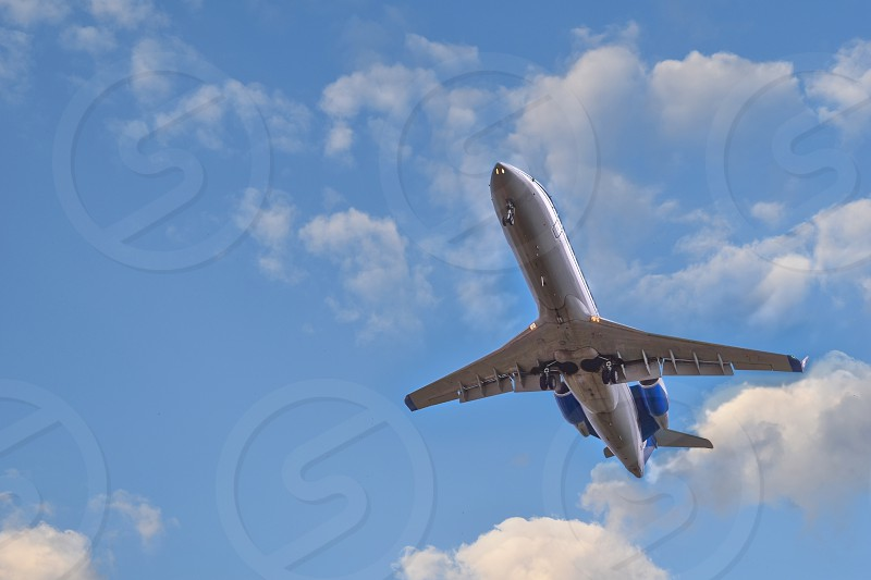 Plane landing. Cloudy blue sky is a background. photo