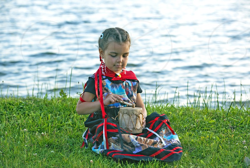 Ojibwe child uses a traditionally made birchbark tom tom drum covered with rawhide next to a lake Midland Ontario Canada photo