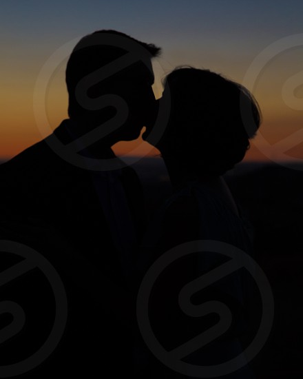 Silhouette of couple kissing at sunset photo