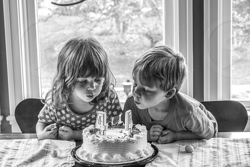 boy and girl blowing cake with number 4 candle photo