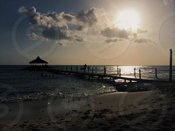sun sunset sky clouds cloud sand dock ocean water photo