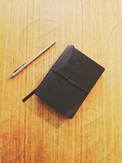black hardbound 2015 planner by silver pen on wooden table photo